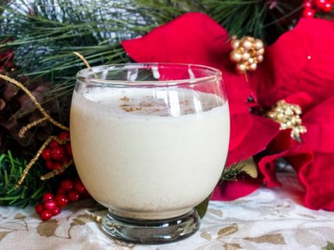 keto eggnog in a small glass with poinsetta in the background