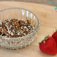 keto cereal ingredients in a glass bowl with two strawberries