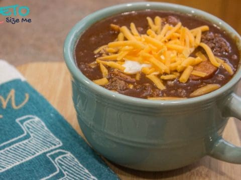 hot keto chili topped with cheddar cheese and sour cream in a mug