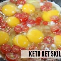 Eggs, bacon, and tomatoes cooking in skillet
