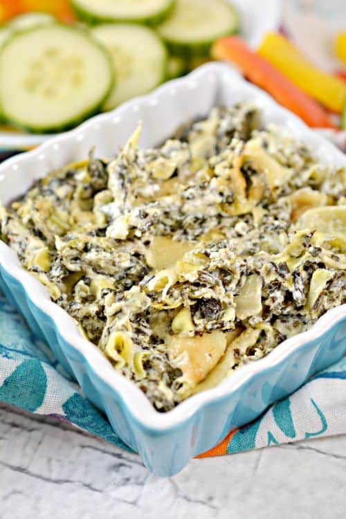 Keto Spinach Artichoke Dip in blue baking dish with cucumbers
